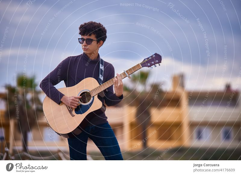 young caucasian teenage boy playing acoustic guitar on the beach. sunglasses and dark clothing. art artist blues casual composer concert entertainment