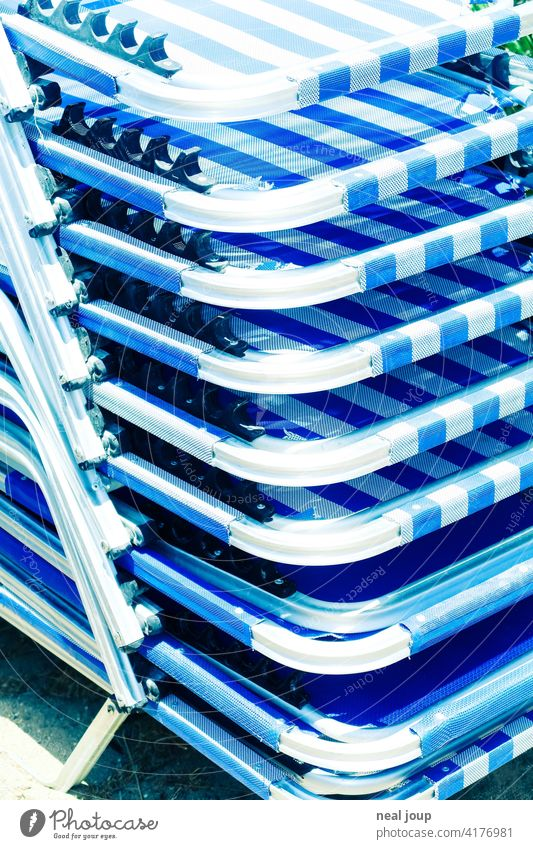 Detail of a stack of blue and white sunbeds in the glaring sunlight vacation Sun Summer sun lounger Stack Blue White Bright Greece detail Glittering Steel Metal