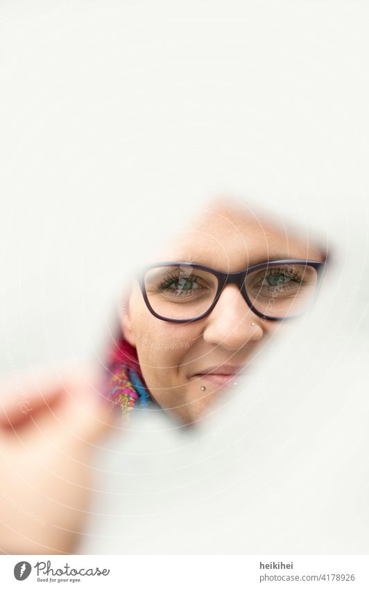 Woman looks friendly through a mirror shard into the camera Mirror Feminine Young woman Human being Adults 18 - 30 years portrait Face Head reflection