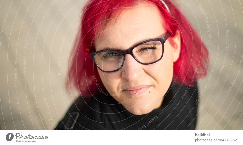 A redheaded woman with glasses and piercings looks into the camera winking Woman Eyeglasses Red-haired portrait Lip piercing conspicuous appearance Emanation