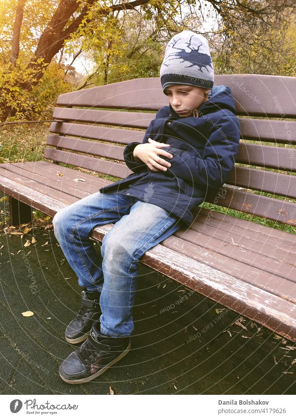 sad boy sitting on bench alone outdoor hopeless remembering thoughtful negative mistake worried despondent adolescent handsome education melancholy teenage