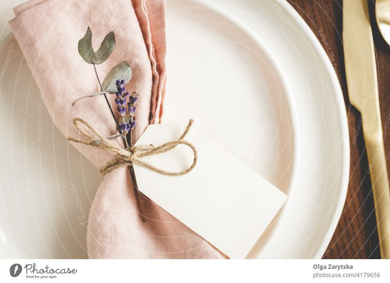 Table setting details on white plates. table setting napkin pink linen floral tag blank lavender close up golden cutlery place setting bow tied eucaliptus rope
