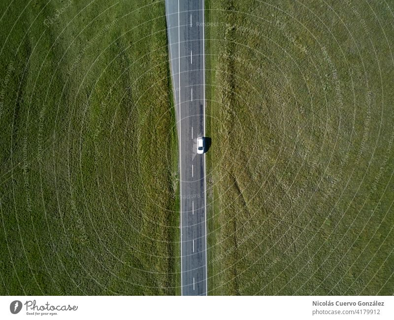 Aerial top view from car riding on straight road with green grass on both sides aerial nature outdoor horizontal driving scale middle tranquility explore colors