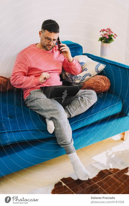 Man teleworking from the sofa at home with the computer due to the coronavirus pandemic telecommuting crown office student study from home covid covi19