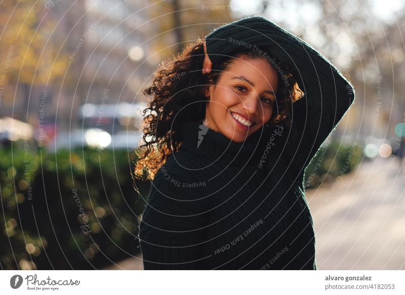 Woman smiling while posing outdoors. young woman urban street sombrero style city closeup curly hair hairstyle clothing trendy one pose confident casual