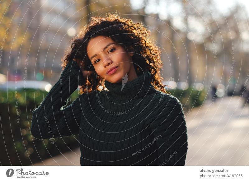 Young woman standing outdoors on the street. young urban sombrero style city closeup curly hair hairstyle warm clothing trendy one posing confident casual