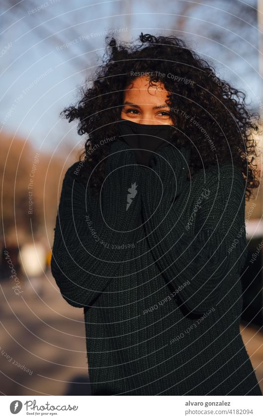 Woman with face mask while standing outdoors. woman urban street covid-19 sombrero style city closeup curly hair warm clothing pandemic new normal protective