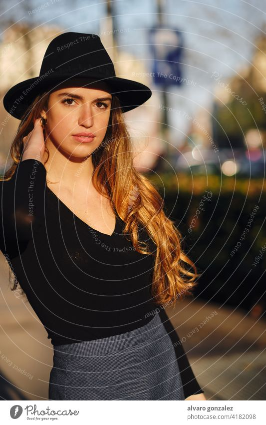 Portrait of young woman posing outdoors. urban street sombrero style city closeup clothing outside one pose confident casual long hair looking lifestyle