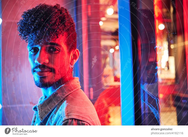 young hispanic man close to a neon light with blue and red lights male model adult people person portrait guy face handsome caucasian attractive background