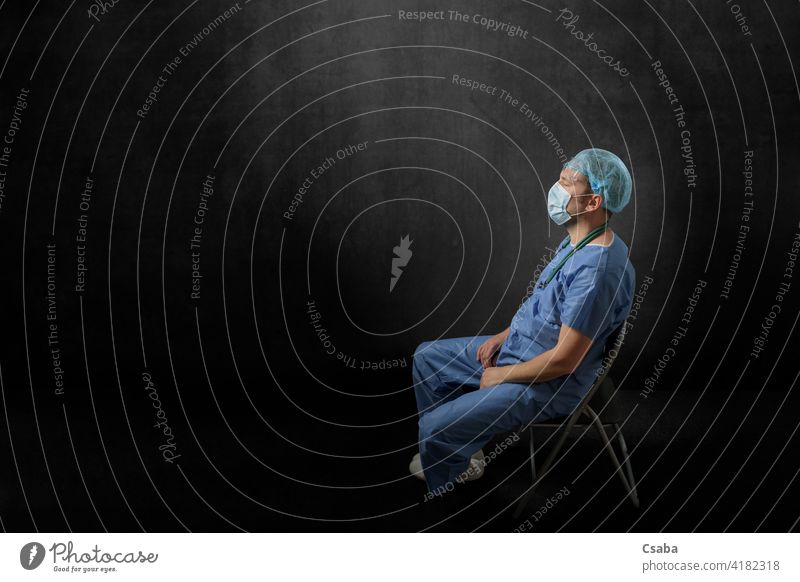 Sad, exhausted doctor sitting in a dark room sad tired man side view disappointed eyes closed pandemic male stress medical epidemic uniform healthcare