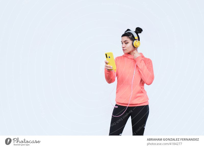 girl fixes her hair using her smartphone as a mirror woman young looking mobile phone appearance holding smile technology one person female beauty young adult