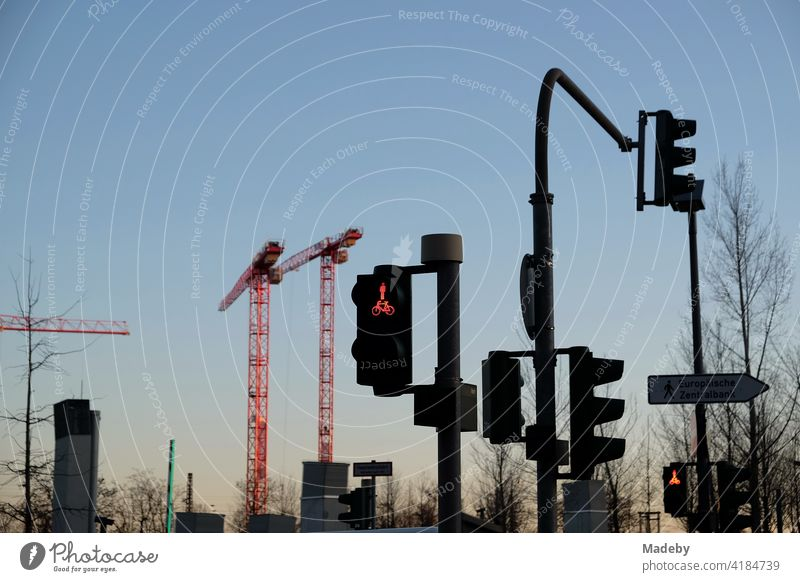 Traffic lights and construction cranes in the light of the setting sun on Hanauer Landstraße in the Ostend district of Frankfurt am Main in the German state of Hesse