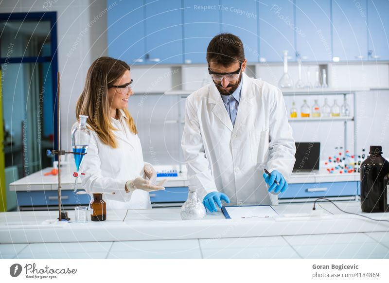 Researchers doing experiment with smoke on a table of a chemical laboratory analysis analyze chemist chemistry danger discovery experimental female formula