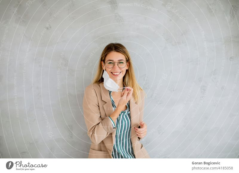 Young woman standning by the grey wall and taking off a respiratory mask from coronavirus disease adult background beautiful beauty caucasian covid19 epidemic