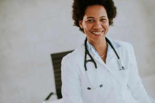 Female African American doctor wearing white coat with stethoscope standing by desk in office adult african american beautiful black clinic computer ethnic