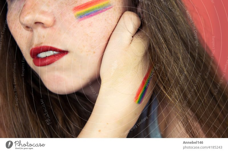 Portrait of a young woman with rainbow Flag on cheek and body, the LGBT community on a colorful pink background fashion hand pastel love person girl face beauty