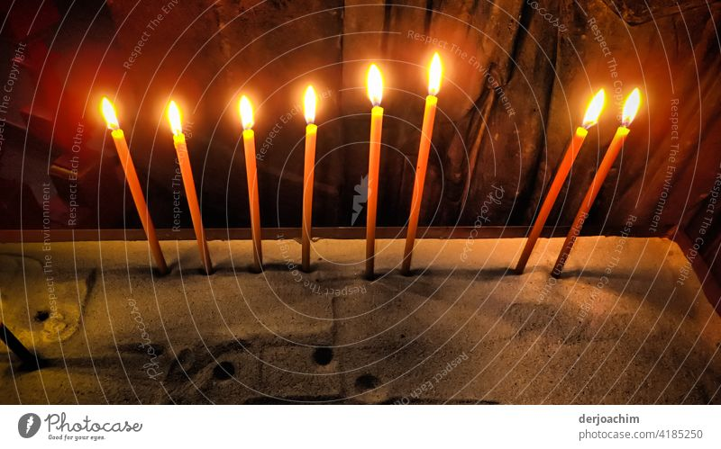 Eight lit candles stuck in the sand. Burn Flame ardor Fire Decompose Colour photo Red Orange Warmth Light Hot Embers Yellow Deserted Night Glow Dangerous
