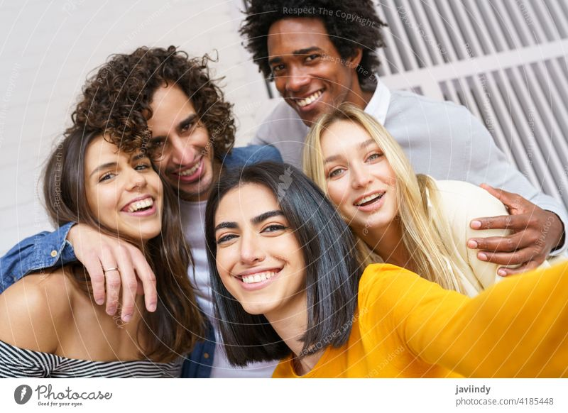 Multi-ethnic group of friends taking a selfie together while having fun outdoors. people smartphone multiracial multi-ethnic caucasian photographing students