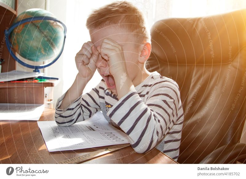 school-age boy crying and screaming while doing homework. the concept of heavy pressure education child student angry stress reading elementary young people kid