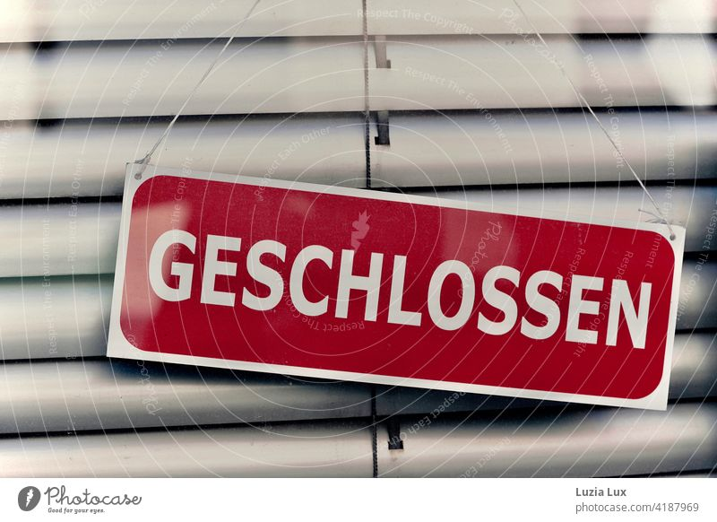Closed: dark red sign in front of lowered blind in a shop door. signage Signage Store premises Characters Front door Retail sector Signs and labeling Entrance