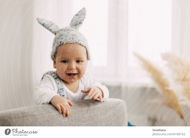Kid in funny easter bunny costume sits in a chair and laughs baby rabbit suit easter eggs game sitting toy child bed interior sleep newborn boy one leaf smiling