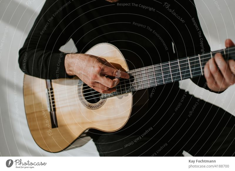 photo of man playing classical guitar acoustic adult arm artist chords closeup expertise fingers flamenco fretboard guitar player guitarist guitarists guitars