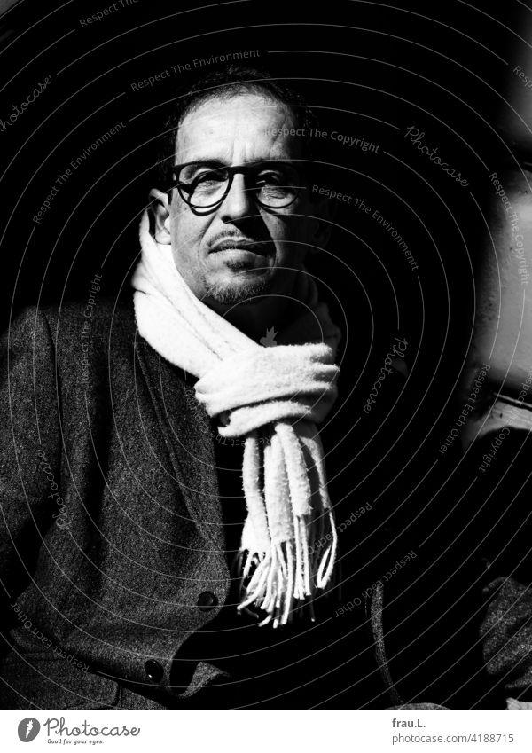 A man with a scarf Winter Eyeglasses Man Face portrait Blazer Jacket seriously sunshine