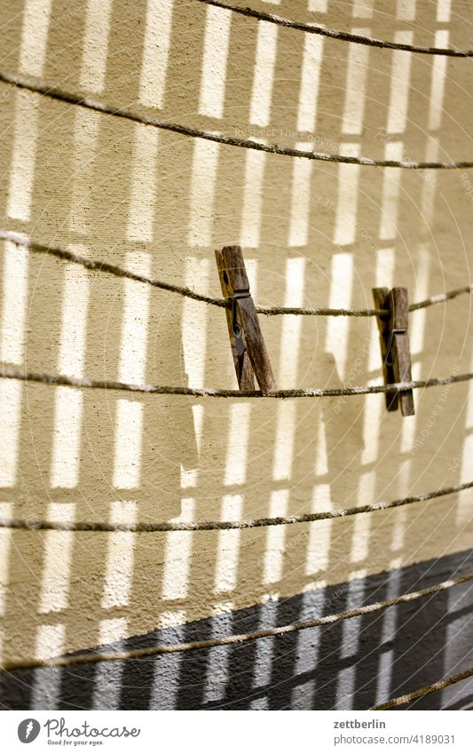 Two clothespins Holder two Pair duo Duet clothesline Cotheshorse Empty Household Light Shadow Wall (building) leash Side by side Wood Old Weathered Washing day