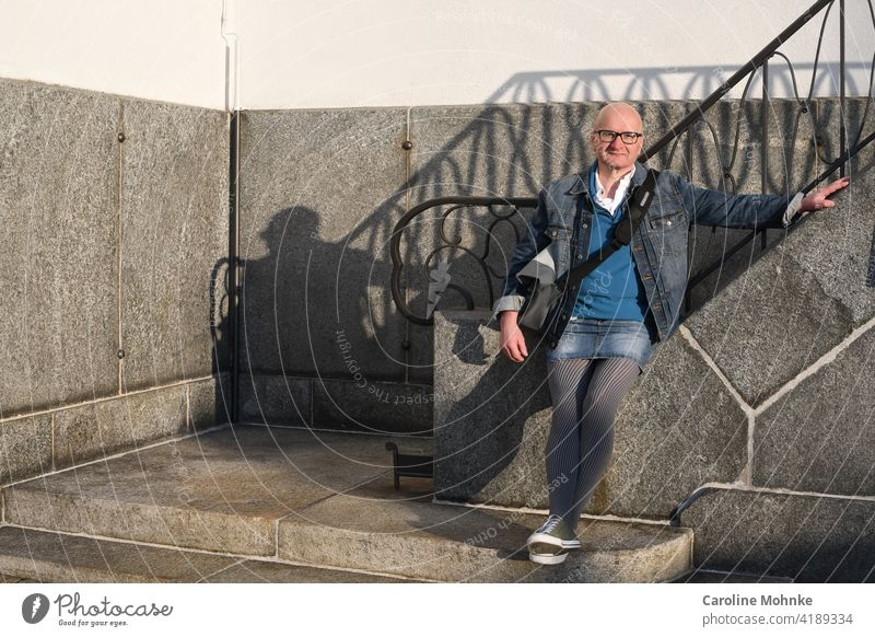Man in denim jacket, denim mini, houndstooth pattern tights and sneakers at a staircase Fashion Individualist Houndstooth Colour photo Exterior shot Day