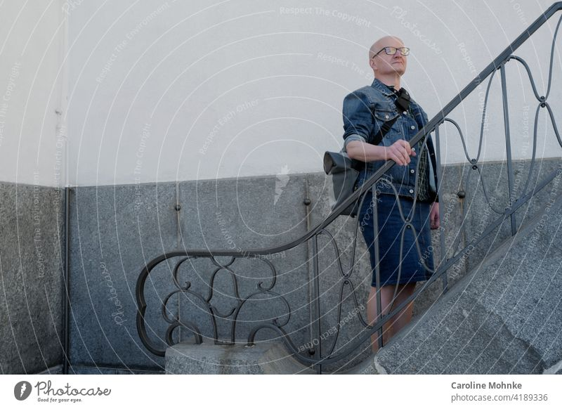 Man in denim jacket and denim skirt stands on a staircase Fashion Individualist Denim skirt Jeans jacket Lifestyle Human being Adults Colour photo Exterior shot