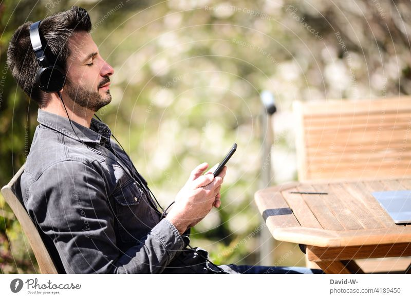 Man listening to music on his mobile phone - relaxation Music stream Listening Cellphone Headphones To enjoy time-out chill Nature Beautiful weather Lifestyle