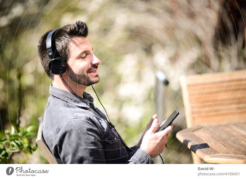 Man streams music via his mobile phone and sings along Music streaming Cellphone Headphones Sing Good mood happy Listen to music Happiness Easygoing Contentment