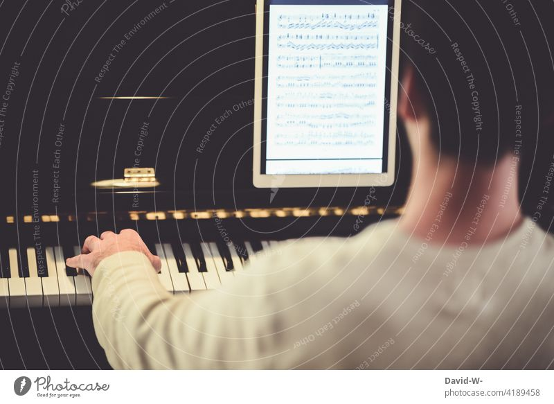 Musician plays the piano Piano Modern technology notes Ipad Electronic Play piano Make music Practice