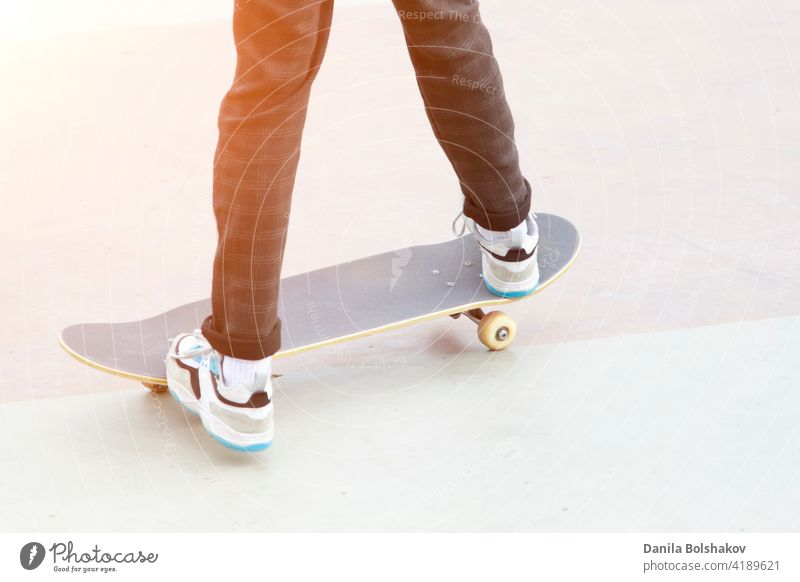 skateboard and legs of man riding on it close up outdoors trendy vintage hipster person practice workout summer exercising enjoyment danger jeans sport