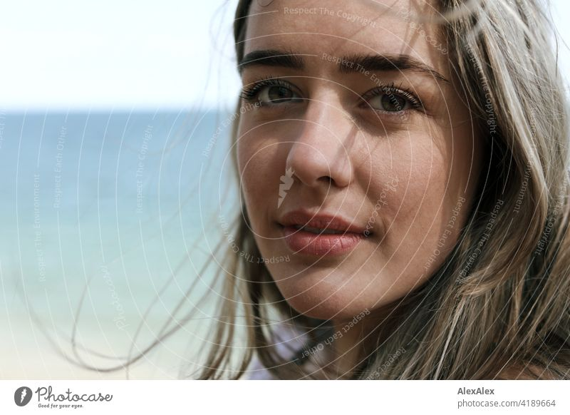 Beautiful blonde girl stands on the beach of the Baltic Sea and looks into the camera Girl Smiling joyfully Landscape Blonde Joy Exterior shot Face Young woman
