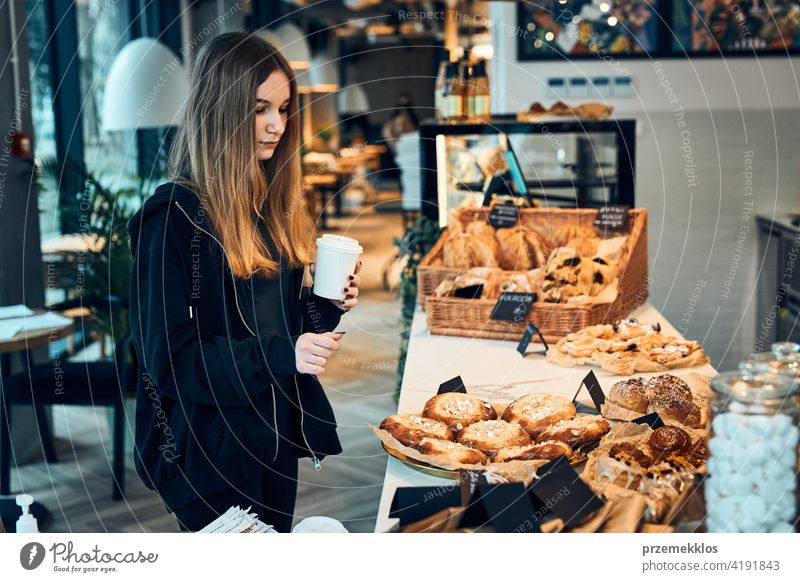 Woman holding cup with coffee looking at pastry, buns, cakes and cookies and waiting for the order. Girl buying a sweet food and hot drink to go. Young woman having a break doing shopping in a coffee shop