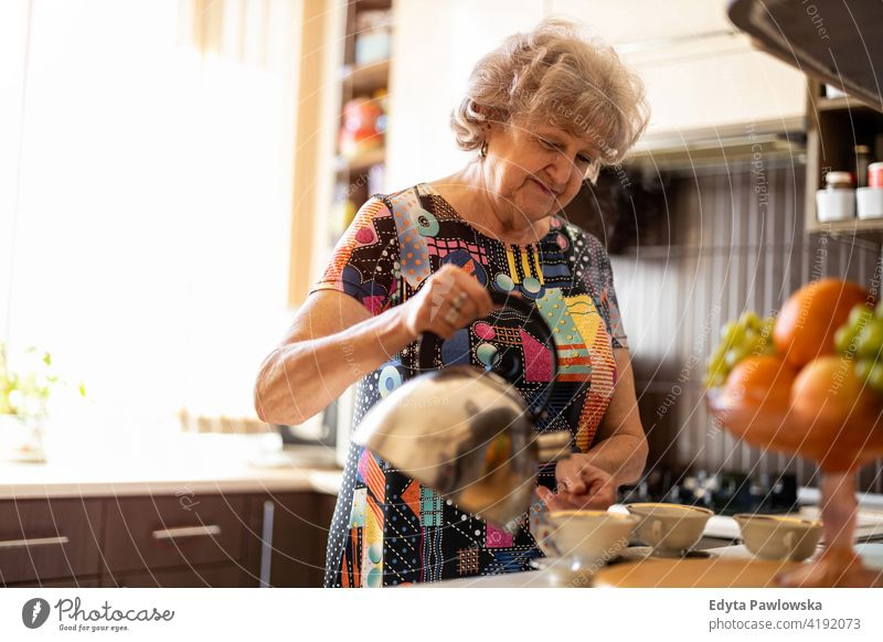 Senior woman with kettle pouring hot water into cup in kitchen preparing tea drink breakfast coffee cup making caffeine morning mug fruit real people candid