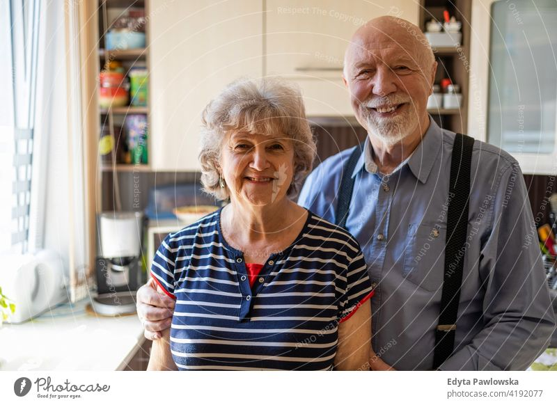 Happy senior couple together at home real people candid genuine woman mature female love bonding Caucasian elderly house old aging domestic life grandmother
