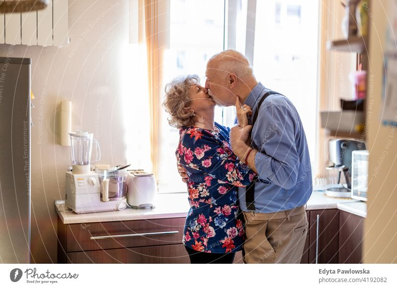 Happy senior couple kissing in the kitchen real people candid genuine woman mature female together love bonding Caucasian elderly home house old aging