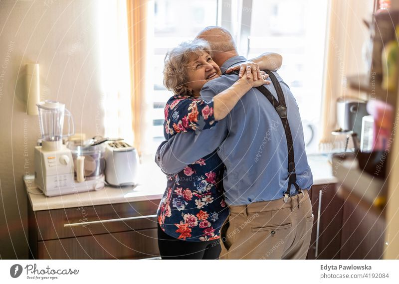 Elderly couple embracing and smiling in the kitchen real people candid genuine woman senior mature female together love bonding Caucasian elderly home house old