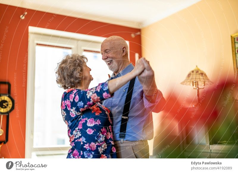 Happy senior couple dancing together at home real people candid genuine woman mature female love bonding Caucasian elderly house old aging domestic life