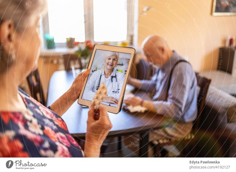 Senior couple consulting with a doctor on digital tablet real people candid genuine woman senior mature female together love bonding Caucasian elderly home