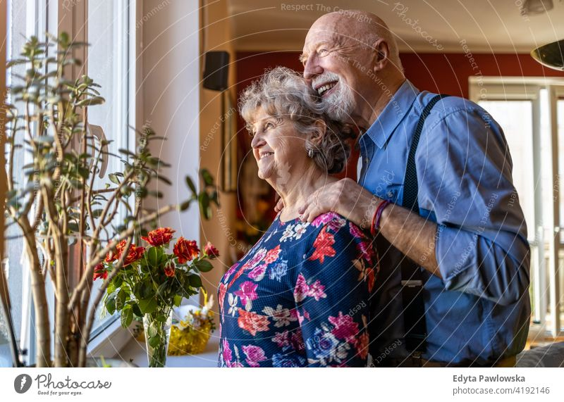 Senior Couple Looking Through Window real people candid genuine woman senior mature female couple together love bonding Caucasian elderly home house old aging