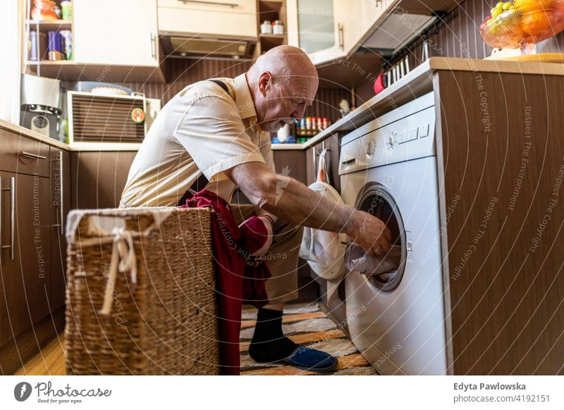 Senior man doing the laundry at home real people candid genuine senior mature male Caucasian elderly house old aging domestic life grandfather pensioner