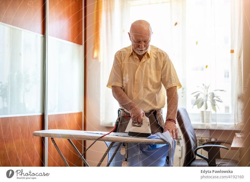 Senior man at home ironing his clothes real people candid genuine senior mature male Caucasian elderly house old aging domestic life grandfather pensioner