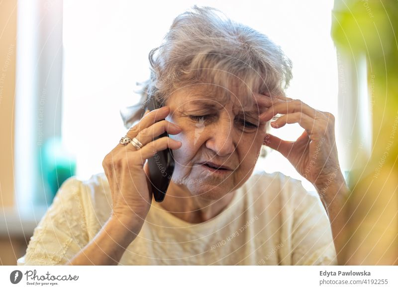 Shot of a tired senior woman using a mobile phone real people candid genuine mature female Caucasian elderly home house old aging domestic life grandmother