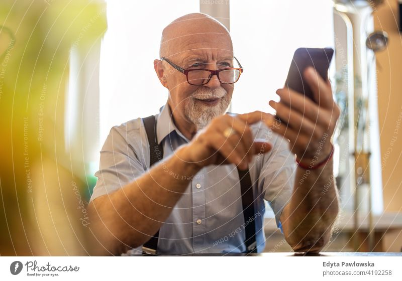 Shot of a senior man using a mobile phone at home smartphone tech technology communication online modern connection wireless real people candid genuine mature