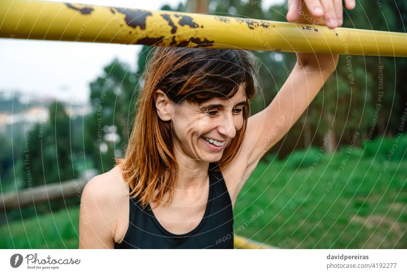 Happy and tired athlete woman after training sportswoman happy smiling proud achievement success recovery supported effort bar slender satisfied exercise