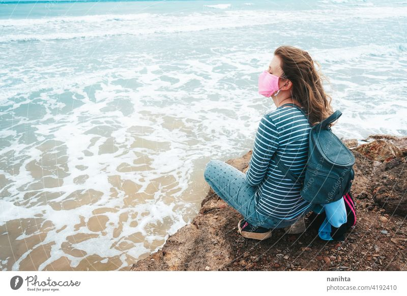 Young woman wearing a pink face mask sitting near the sea hope brave strong covid coronavirus beach ocecan free freedom survivor hopeful dream health medical