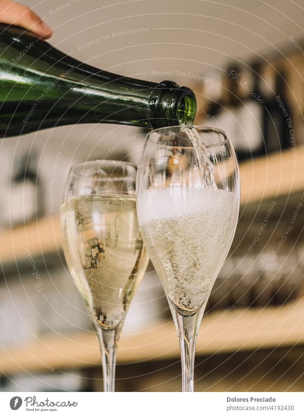 A waiter serving two glasses of Spanish champagne known as cava of Catalan origin champagne new year champagne flute elegance valentine's day bottle elegant